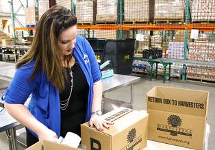 Azura associate helping package Harvester's boxes in Topeka