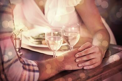 Couple holding hands at dinner at home in the dining room.jpeg