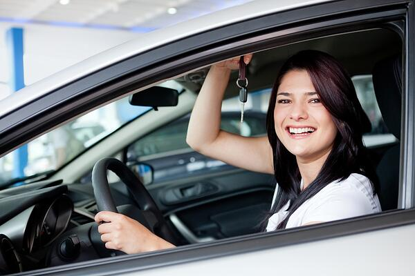 Excited woman buying a car and holding keys